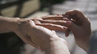 Close-up hands of senior couple during engagement with diamond ring. Elderly male holding hand of his senior fiancee girlfriend and putting beautiful engagement ring on finger while marriage proposal