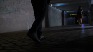 Close-up legs of male criminal walking in dark underpass passage following lonely female at night. Attacker chasing his victim in underground station as she walks alone after party. Steadicam