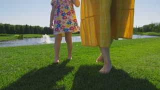 Close-up legs of mother in casual dress and little toddler stepping and walking on green grass barefoot. Child running around mom's legs as family walks on green meadow near pond in summer. Steadicam