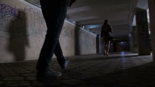 Close-up male attacker legs following young female in mini skirt at night in dark pedestrian underpass. Scared female looking back at criminal and starts running. Steadicam shot