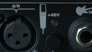 Close-up male finger pressing switchable 48V phantom power on black Audio Interface. Phantom power supply.