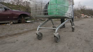 Close-up male legs pushing shopping cart with plastic bags at garbage dump with abandoned cars. Homeless man scavenging at landfill. Homelessness and environmental problems concept. Steadicam shot.