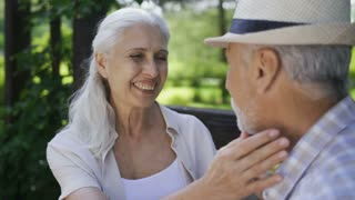 Close-up of affectionate senior couple sitting outdoors, talking about love, flirting and kissing. Beautiful woman with white hair touching husband's face gently as they relax in nature during travel