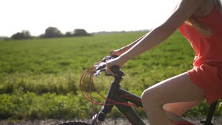 Close-up of blonde teen girl in glasses on a bicycle adventure through green fields in countryside. Peaceful teenage girl enjoying bike ride during summer holidays. Steadicam shot