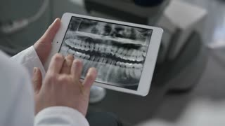 Close-up of dentists's hands holding and using tablet pc. Medical doctors discussing patient's diognosis and teeth problems on the basis of dental x-ray on touchpad at dental office