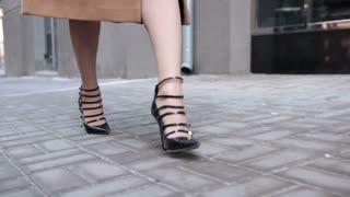 Close up of elegant female legs walking in street