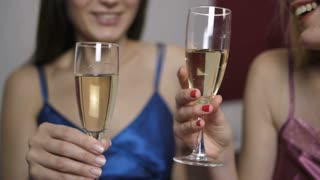 Close-up of female best friends in lingerie chatting, laughing and toasting champagne together in bedroom. Happy positive women clinking champagne glasses and drinking. Slow motion. Dolly shot
