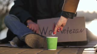 Close-up of legs, hands and cardboard sign of disabled war veteran asking for help on the pavement. Homeless man sitting with sign and paper cup begging for money. Female throwing coins into cup.