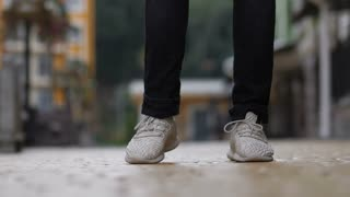 Close-up of male dancer legs in white sneakers performing street afrohouse dance on cobblestone sidewalk over blurry urbanscape background. Low angle view. Man dancing freestyle dance on city street