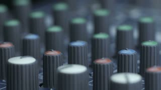 Close-up of male fingers turning equalizer knobs on audio mixing desk. Shot with multiple equalizer and fader knobs.