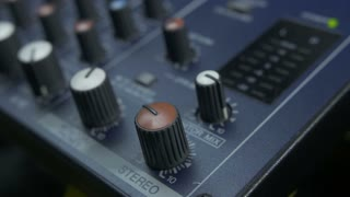 Close-up of male fingers turning fader knob on audio mixing desk. Peak level meters of an analog mixer console visible.