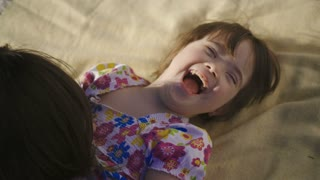 Close-up of mother and special needs daughter playing on blanket outdoors. Mom tickling laughing down syndrome girl making her laugh and smile. Sweet family relaxing and enjoying together outdoors
