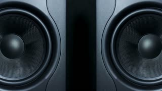 Close-up of two black round audio speakers vibrating from sound on low frequency. Modern sub-woofers.