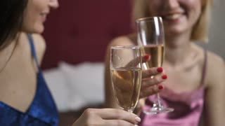 Close-up of young happy female couple celebrating anniversary together with champagne in home interior. Smiling talking women in lingerie clinking glasses and toasting champagne. Slow motion. Dolly