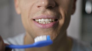 Close-up of young male's mouth as he brushes white natural teeth with blue toothbrush. Toothbrush moving up and down brushing teeth and man smiles to the camera with white toothy smile.