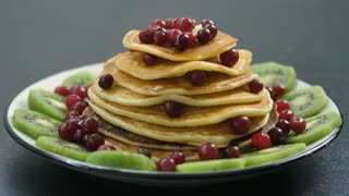 Close-up pancakes stack on plate being decorated with cranberries and dusted with powdered sugar. Sweet american morning breakfast from homemade pancakes
