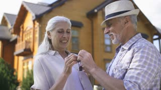 Close-up portrait of attractive senior aged couple in front of new house standing and showing door key to camera while smiling. Rack focus from elderly wife and husband to house keys while shaking.