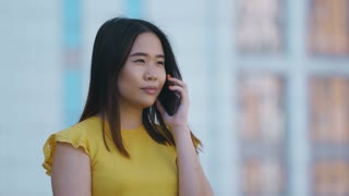 Close-up portrait of attractive young asian business lady talking on mobile phone outdoors on business center background. Successful female executive smiling having a business call on cellphone