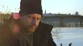 Close-up portrait of mature bearded homeless man looking at camera during sunset. Sad abandoned male in hat and jacket with despair and sorrow in his eyes. Homelessness and social issues concept.