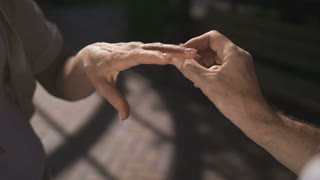 Close-up senior hands outdoors while elderly man proposing his woman and putting engagement ring on her finger. Romantic elderly male making marriage proposal to girlfriend with diamond ring.