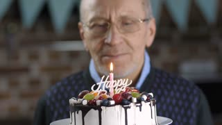 Close-up view of handsome senior man in eyeglasses thinking about life and blowing a candle on his birthday cake. Birthday party of thoughtful elderly grandfather at home