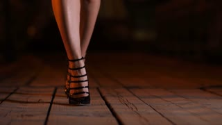 Close-up woman's legs in black retro stiletto shoes with high heels walking at night on city bridge on bokeh light background. Slim beautiful female feet strolling alone at night. Steadicam stabilized