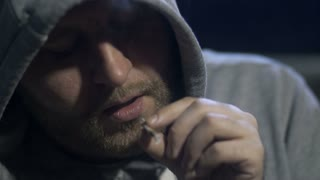 Close-up young male portrait smoking marijuana joint at home in a domestic room at night. Addicted man in a hooded shirt inhaling cannabis smoke. Social issues and drug addiction concept