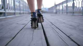Closeup back view of sexy female feet in high heeled shoes walking on urban wooden city bridge. Seductive slim legs of businesswoman strolling in city. Lady going for a date in stiletto shoes