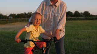 Closeup cute smiling and happy little toddler boy learning to ride a bicycle with helping hand of grandmother assisting him. Granny teaching her grandson to cycle in nature during beautiful sunset.