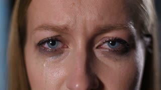 Closeup portrait of adult woman with deep sorrowful blue eyes staring into the distance as mascara runs down her face. Upset depressed female looking at camera, tears and makeup running down her face.