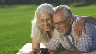 Closeup portrait of happy senior couple lying on green lawn and using smarphone. Elderly man and woman with gray hair using modern device, laughing and enjoying technology while sharing travel photos