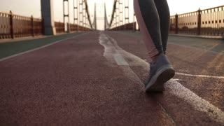 Closeup rear view of female legs in sneakers jogging across city bridge early morning at sunrise. Active fit woman's legs and feet running. Sport, healthy lifestyle concept. Steadicam stabilized shot