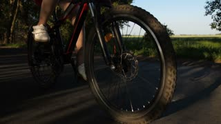 Closeup shot of teen girl legs riding bicycle on countryside road. Bike wheels spinning as teenage female cycling on rural road at sunset. Steadicam shot