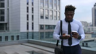 Coffee break on a go. Smiling african american businessman holding coffee cup and checking news on smart phone while walking outdoors. Positive entrepreneur networking with cellphone on city street.
