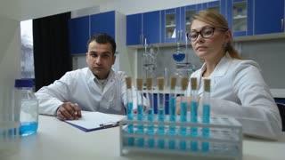 Confident scientists examining solution in lab
