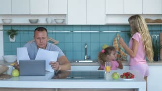 Confused man with laptop analyzing home finances
