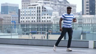 Cool trendy african american guy in headphones performing afrohouse dance on city street. Happy black male hipster dancing in afrobeat style outdoors over urbanscape background. Slow motion.