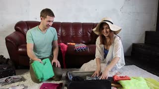 Couple packing for holiday trip and having fun