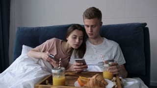 Couple sharing phone watching media content in bed