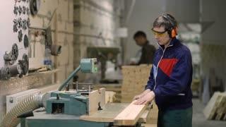 Craftsman cutting wooden plank with circular saw