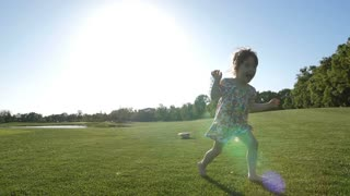 Cute and sweet little toddler girl with down syndrome running towards camera in dress during sunset. Excited happy special needs child running barefoot on green grass and enjoying time in park. Slo mo