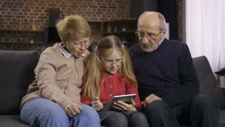 Cute blond hair teenage girl sitting on sofa together with grandparents teaching them to use touchpad. Sweet granddaughter explaining how to search and browse online on internet on tablet pc. Dolly