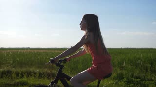 Cute blonde teen girl riding bike in countryside at sunset. Stylish teenage female on a bicycle enjoying nature and riding through summer field during holidays. Blue sky on background. Steadicam shot