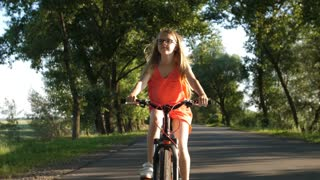 Cute blonde teenage girl in glasses on a bicycle trip in summer countryside. Sweet teen girl enjoying views of nature while riding a bike on rural road. Steadicam shot. Front view