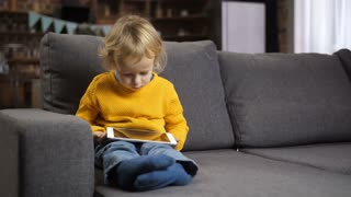 Cute concentrated little toddler boy sitting on comfortable sofa in domestic room with touchpad on his lap. Sweet blond hair boy in yellow jumper watching a cartoon on tablet pc. Dolly shot