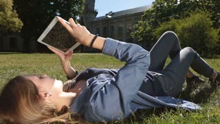 Cute female student studying with tablet in park