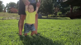 Cute infant taking first steps with father's help