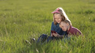 Cute kids playing on smartphones sitting on grass