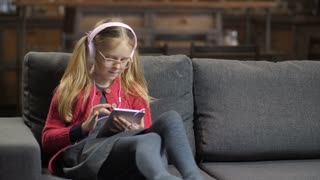 Cute little girl in pink headphones and eyeglasses sitting on the sofa and using digital tablet pc. Blond teenage girl surfing the net and e-learning with touchpad in domestic room on the couch.