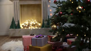 Cute little girl looking for gifts under Xmas tree